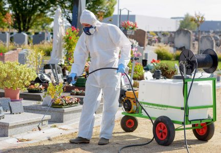Worker Wearing Safety Gear while Spraying Pesticide