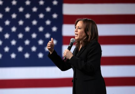 U.S. Senator Kamala Harris speaking with giant American flag behind her.