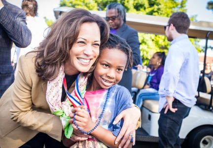 Kamala Harris poses with a young child at event.