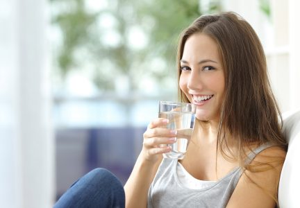 Woman Smiles while Drinking Water filled with PFAs